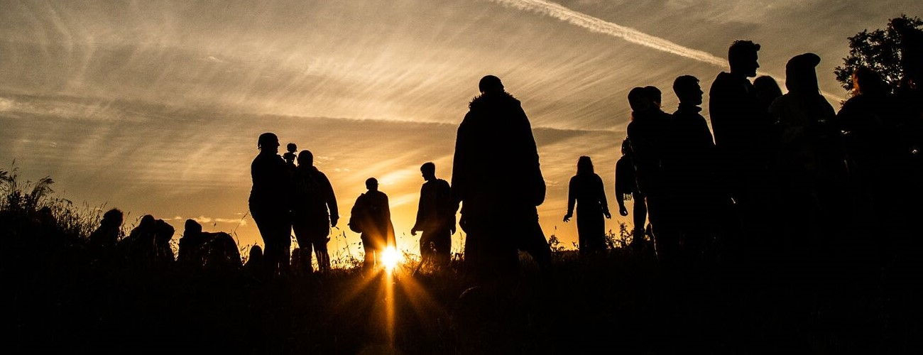 worshippers silhouetted by the rising sun at avebury on solstice morning