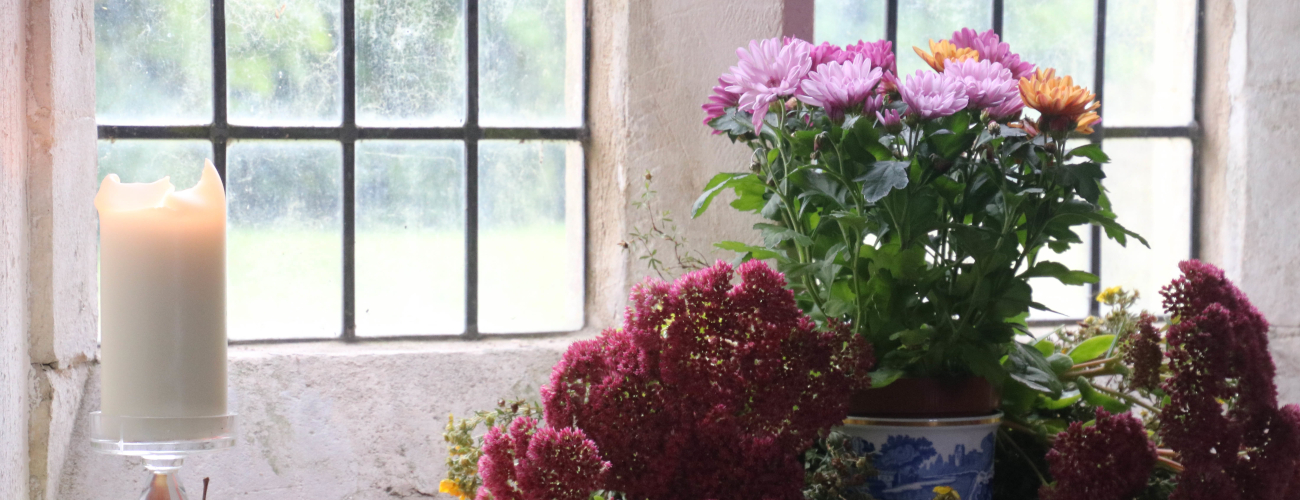 candle and flowers in window of WInterbourne monkton