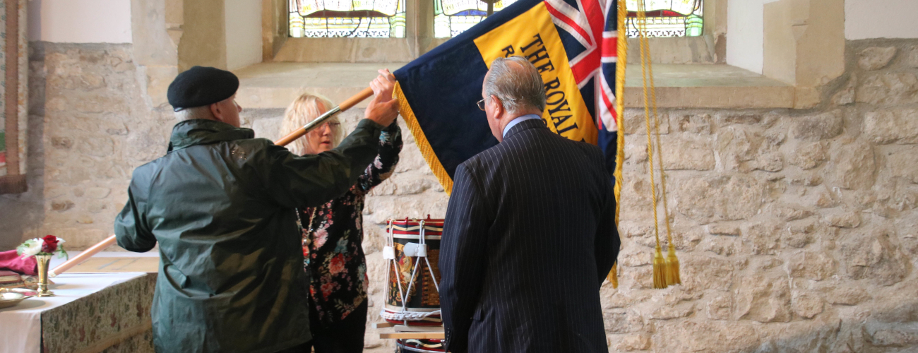 Rev Maria and two members of the British legion holding their flag