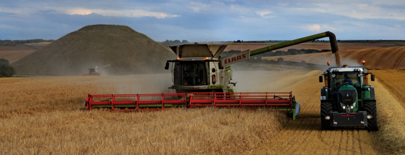 foreground: a combine harvester emptying grain into a trailer, Background: silbury hill